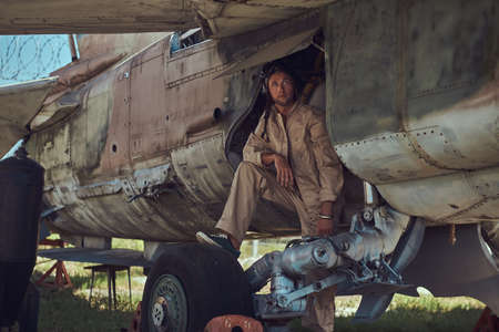 Mechanic in uniform and flight helmet carries out maintenance of an old military bomber.