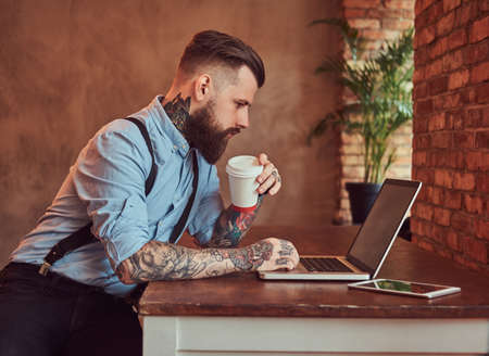 Handsome tattooed hipster in a shirt and suspenders sitting at the desk, working on a laptop, holds takeaway coffee in an office with a loft interior.