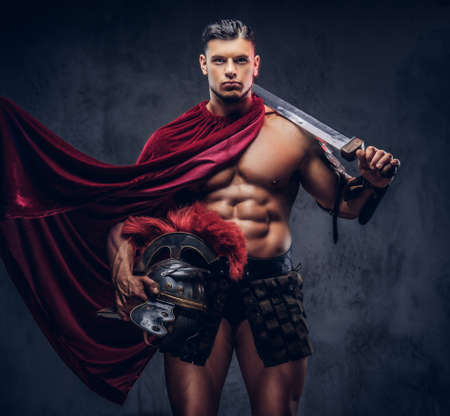 Brutal ancient Greece warrior with a muscular body in battle uniforms 스톡 콘텐츠