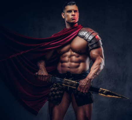 Brutal ancient Greece warrior with a muscular body in battle uniforms Foto de archivo