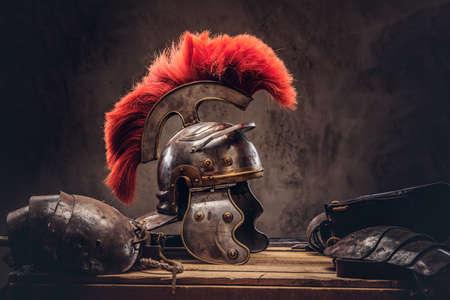 Complete gevechtsuitrusting van de oude Griekse krijger ligt op een doos met houten planken.