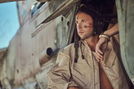 Portrait of a mechanic in uniform and flying near, standing under an old bomber airplane .