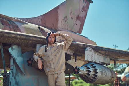 Pilot in uniform and flying helmet standing near an old war fighter-interceptor. Stock Photo