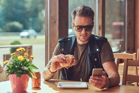 Handsome hipster with a stylish haircut and beard sits at a table, decided to dine at a roadside cafe, using a smartphone while eating a hamburger.