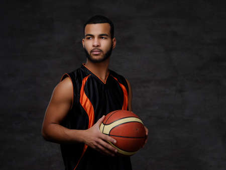 Young African-American basketball player in sportswear isolated over dark background. Standard-Bild