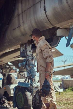 Mechanic in uniform standing near a war fighter-interceptor.