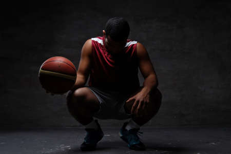 African-American basketball player in sportswear squatting with a ball on a dark background. Foto de archivo
