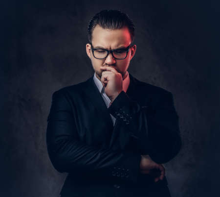 Close-up portrait of a thoughtful stylish businessman with serious face in an elegant formal suit and glasses on a dark background. 스톡 콘텐츠