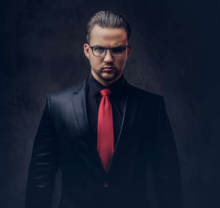 Portrait of a stylish male in a black suit and red tie. Isolated..