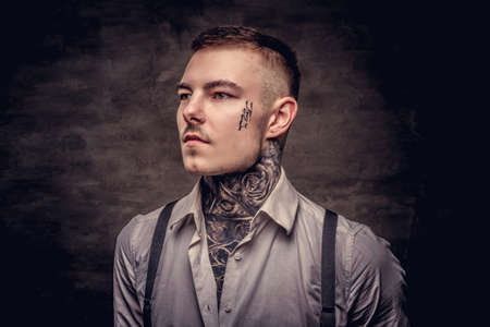 Close-up portrait of a young old-fashioned tattooed guy wearing white shirt and suspenders. Isolated on dark background. Stockfoto