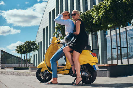 Beautiful couple - handsome stylish guy dressed in a white shirt and jeans and charming blonde woman wearing black dress sitting together on a yellow classic Italian scooter against a skyscraper. Summer Europe vacation, date, romance.