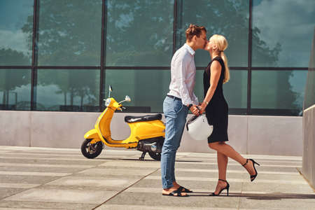 Beautiful couple in love - handsome stylish guy dressed in a white shirt and jeans and charming blonde girl wearing black dress hold hands and kiss against a skyscraper.