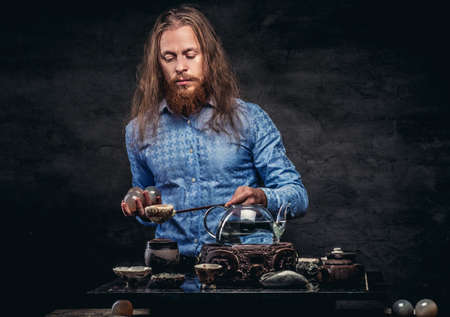 Tea ceremony concept. Portrait of a redhead hipster male with long hair and full beard dressed in a blue shirt, concentrates on making tea, using a handmade tea set. Isolated on dark textured background.