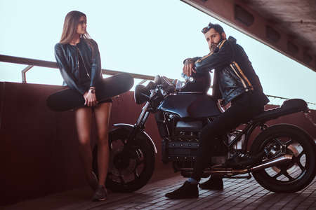 Portrait of an attractive couple - brutal bearded biker in black leather jacket sitting on a motorcycle and his young sensual brunette girlfriend holds skateboard on a footway under a bridge, looking at camera. Stok Fotoğraf