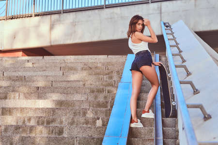Back view of a sensual girl dressed in shorts and t-shirt holds a skateboard posing at camera while standing on steps.