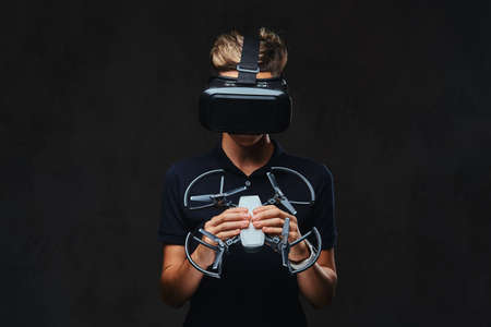 Young teenager dressed in a black t-shirt wears virtual reality glasses and holds a quadcopter. Isolated on a dark background.
