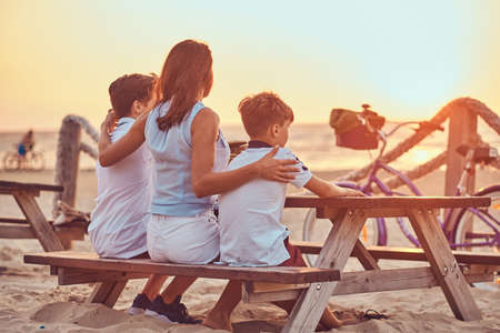 Back view of a cute family - mother with her sons sitting on a bench and looks at the bright sunset on the seacoast.