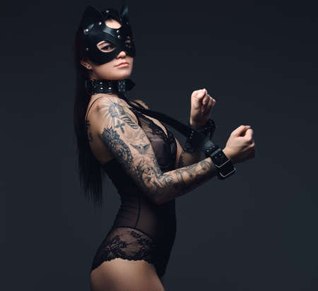 Sexy woman wearing black lingerie in BDSM cat leather mask and accessories posing on dark background.