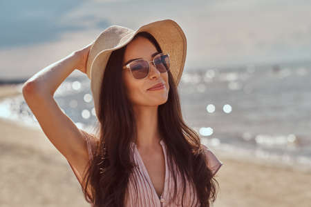 Portrait of a smiling beautiful brunette girl with long hair in sunglasses and sunglasses wearing a dress on the beach.