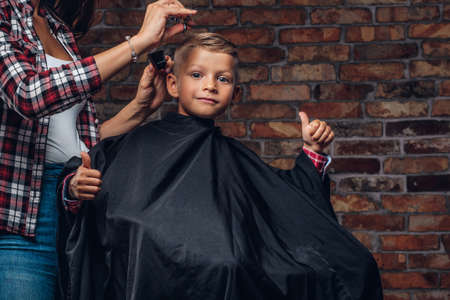 Contented cute preschooler boy shows thumbs up while getting a haircut. Children hairdresser with scissors and comb is cutting little boy in the room with loft interior. Фото со стока