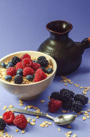 Healthy breakfast. White plate with oatmeal strewn and different berries on a blue background. Standard-Bild
