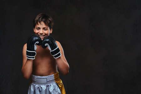 Glücklicher hübscher hemdloser junger Boxer, der Handschuhe trägt. Auf einem dunklen Hintergrund isoliert.