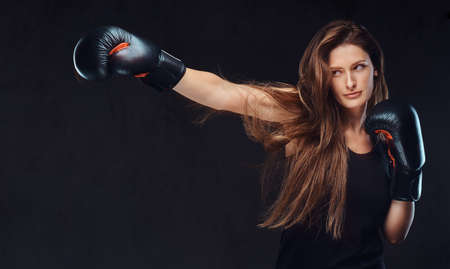 Beautiful brunette female boxer during boxing exercises, focused on a process with serious concentrated facial.