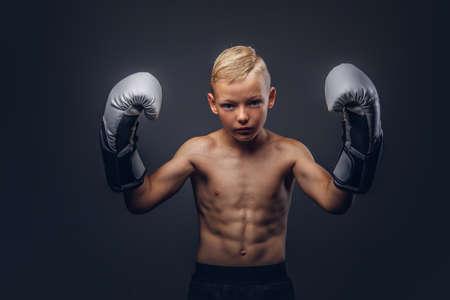 boxeador chico joven sin camisa con los guantes de boxeo posando en un estudio Foto de archivo