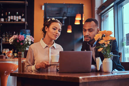 Attractive African-American couple at a business meeting in the restaurant discussing working moments with laptop at lunchtime.