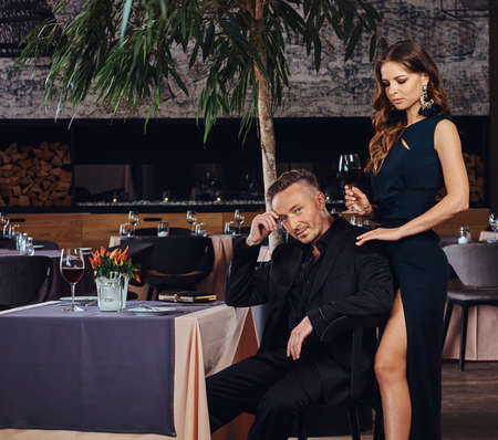 Charming brunette in a black dress is standing by her man who sits at a table in a luxury restaurant.