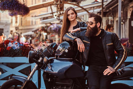 Attractive hipster couple - bearded brutal male in sunglasses dressed in a black leather jacket and his young sensual girl standing near, posing against terrace of cafe. Stock Photo