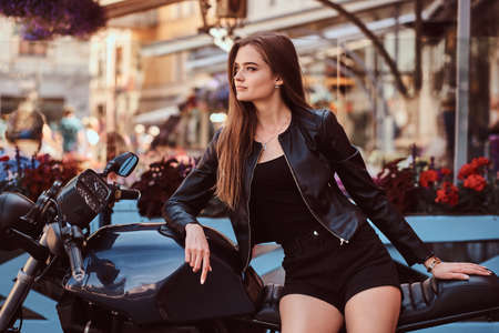 Sensual young girl model dressed in a black dress and leather jacket sitting on custom-made motorcycle, posing against terrace of a cafe. Stock Photo
