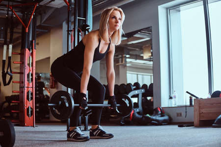 Blonde sportive female in sportswear doing deadlift with barbell in the fitness club or gym.