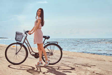 Smiling charming girl dressed in dress walks with her bicycle on the beach at a sunny day.