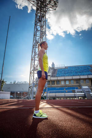 Sportswoman wearing t-shirt and shorts standing on a red running track in athletics stadium. Stock Photo