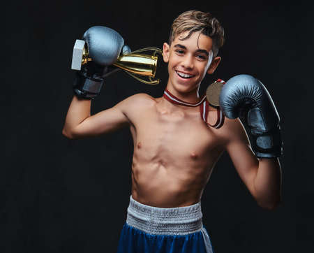 Joyful young shirtless boxer champion wearing gloves holds a winners cup and the gold medal. Isolated on a dark background.