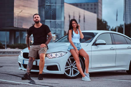 Cool couple - brutal tattooed male and sensual girl leaning on a luxury car outdoors against the skyscraper.