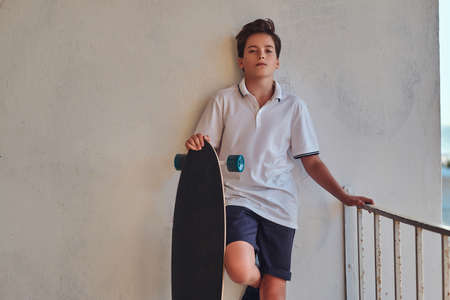 Young skater boy dressed in t-shirt and shorts leaning on the wall.