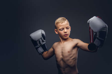 Young shirtless boy boxer in boxing gloves holds a golden medal posing in a studio.