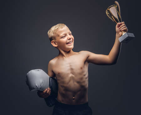 Joyful shirtless boy holds boxer gloves and the winners cup.