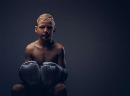 Young shirtless boy wearing boxing gloves sitting on a chair.