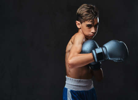 Handsome shirtless young boxer during boxing exercises, focused on process with serious concentrated facial. Stockfoto