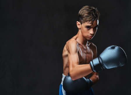 Handsome shirtless young boxer during boxing exercises, focused on process with serious concentrated facial. Stock Photo - 107522813