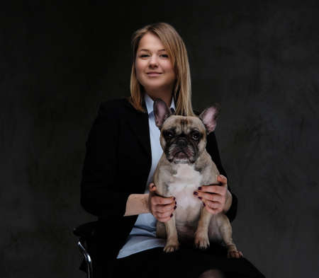 Happy blonde woman breeder sitting on a chair and holds her cute pug. Stock Photo