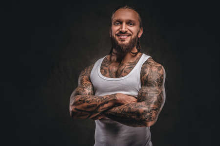 Smiling handsome bearded tattooed male in white shirt posing with crossed arms. Isolated on a dark textured background.