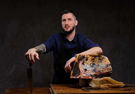 Chef cook holds knife and posing near a table with exclusive jerky meat on a dark background.