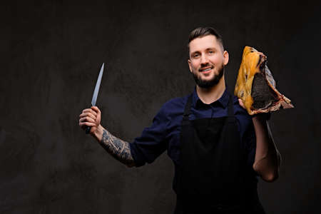 Smirking chef cook holds knife and large piece of exclusive cured meat on dark background.