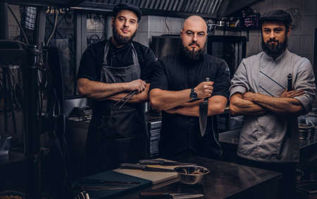 Team of professional bearded cooks dressed in uniforms posing with knives in kitchen. Stockfoto