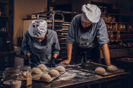 Cooking master class in bakery. Chef with his assistant showing ready samples of baking test in kitchen. Stock Photo