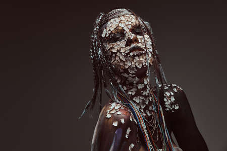 Portrait of a scary African shaman female with a petrified cracked skin and dreadlocks. Make-up concept. Stock Photo